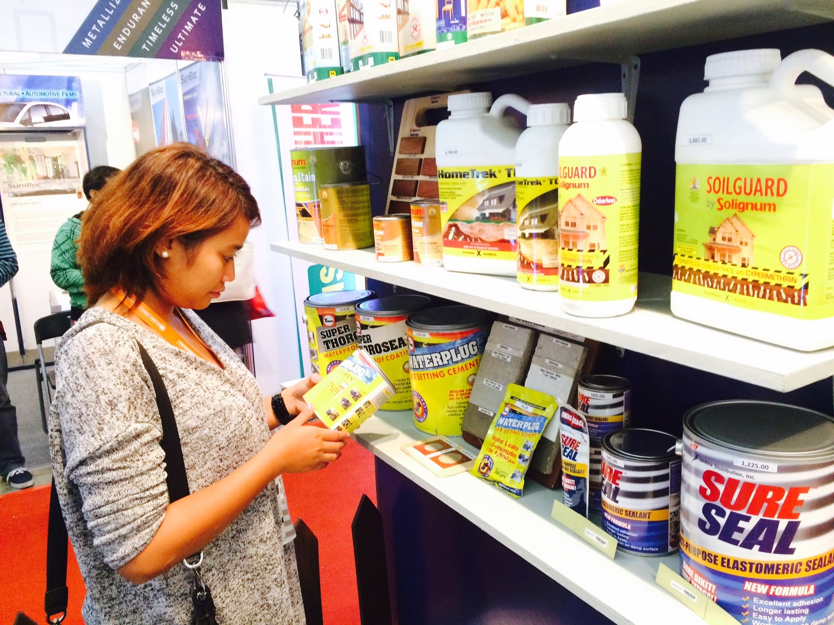 An interested buyer checks out different waterproofing and wood preservation products of Jardine that are on sale during the expo